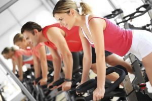 Group-of-people-taking-part-in-spinning-class-in-gym