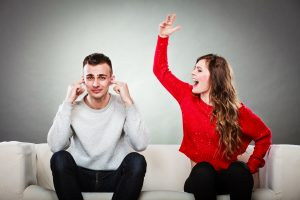 couple having argument - conflict bad relationships. Angry fury woman screaming man closes his ears.
