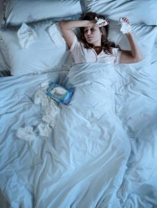 Woman-with-a-cold-lying-in-bed-holding-tissues