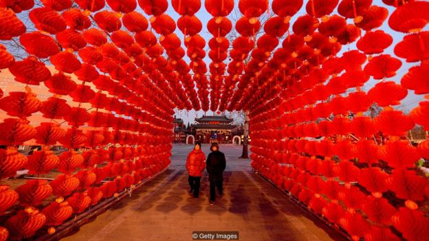A couple walk beneath a display of lanterns for the Lunar New Year as China prepares for the Year of the Horse in Beijing on January 28, 2014. China is preparing to welcome the Lunar New Year of the Horse which falls on January 31 and will see about 3.62 billion trips made by Chinese travelers during the 40-day Spring Festival travel period. AFP PHOTO/Mark RALSTON (Photo credit should read MARK RALSTON/AFP/Getty Images)